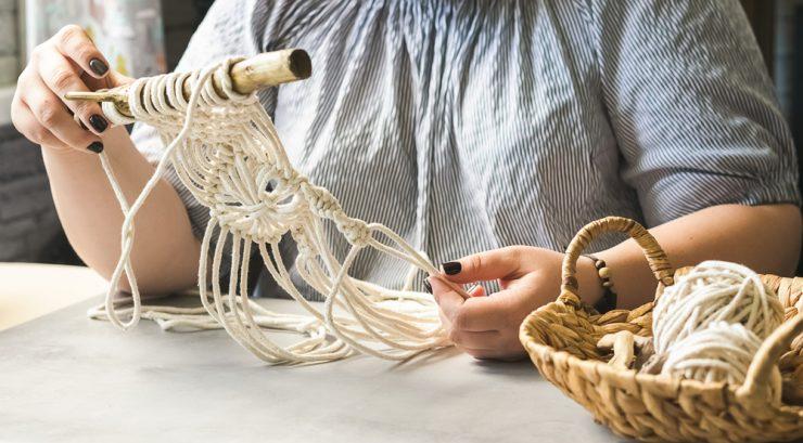 Moda sustentável: um par de mãos brancas segura um objeto artesanal feito com fios de cor clara.