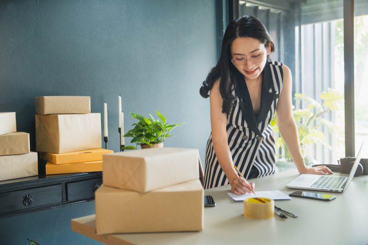 Cursos remotos: na imagem, uma mulher jovem, branca, de cabelos pretos e vestido listrado faz anotações em um bloco de notas, ao lado de um notebook. No primeiro plano da foto, há várias caixas.