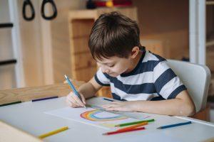 Contraturno no Criar Sesc: um menino branco e de cabelos castanhos desenha um arco-íris em uma mesa branca. Ele usa camisa listrada e segura um lápis azul.