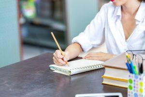 Curso de idiomas: uma pessoa escreve em um caderno com um lápis. Na foto, apenas os braços estão visíveis. Eles são brancos e trajam uma camisa social branca.