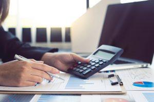 Créditos fiscais: um par de mãos brancas anota informações em um papel com gráficos e segura uma calculadora