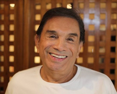 Dedé Santana sorri para a câmera. Ele está em frente a uma porta de madeira, tem cabelos pretos e cursos e usa uma camisa branca.
