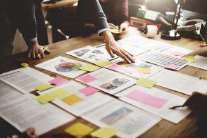 Sem burocracia: imagem mostra um par de mãos organizando vários papéis em uma mesa