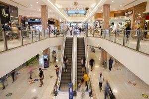 inovação: na imagem, vista de shopping com escadas rolantes, lojas e pessoas passando