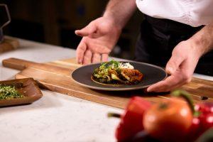 Festival Sabores: um par de mãos segura um prato preto em cima a uma tábua de madeira.