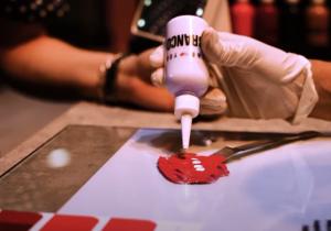 Acessibilidade: a imagem mostra uma mão com luva descartável depositando o conteúdo de um pote branc em uma superfície vermelha, uma das partes da fabricação de batons