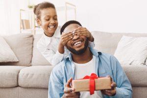 Dia dos pais: uma menina sorri enquanto cobre os olhos do pai com as mãos. Ele segura um presente com um laço vermelho. Ambos são negros, usam roupas claras e estão muito sorridentes.