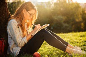 escrita criativa: na imagem, mulher sentada com caderno sobre as pernas enquanto escreve