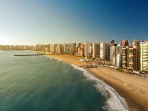 Dia Mundial do Turismo: imagem aérea da Praia de Iracema, em Fortaleza, em um dia de sol. Há prédios na orla, além de uma extensa faixa de areia.