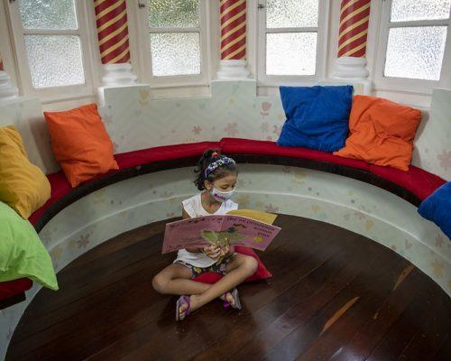 Espaço Mais Infância: uma menina de máscara de proteção, camiseta branca e short colorido lê um livro sentada no chão. Ao redor dela, há várias almofadas coloridas.