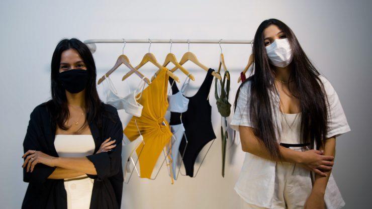 Sustentabilidade: as sócias da Fave Bikini posam para a câmera em frente a uma arara com vários maiôs e biquinis. Elas usam bodies de cores claras, kimonos e máscaras de proteção. Ambas tem pele clara, cabelos pretos, longos e lisos.