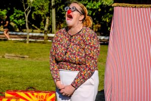 Circo: mulher vestida de palhaça encenando uma cena