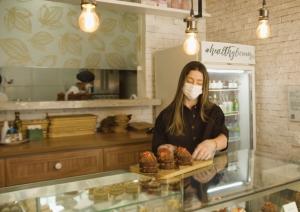 Cacao Saudável: foto da loja da Cacao Saudável. Uma mulher loira com máscara de tecido organiza doces em um balcão.