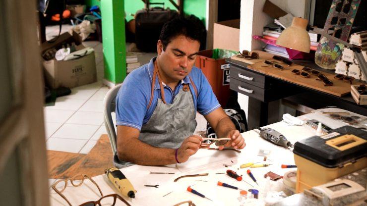 Sustentabilidade: um homem de camisa azul e avental cinza monta uma armação de óculos em uma mesa. Na mesa, há vários instrumentos de montagem, como chaves de fenda