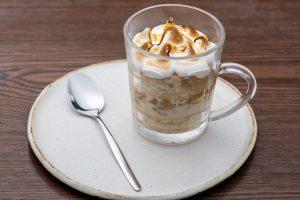 Café Senac: uma xícara transparente com um café cremoso em um prato branco, ao lado de uma colher