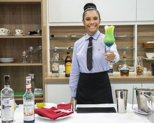 Competições Senac: na imagem, mulher profissional de restaurante segurando taça com drink