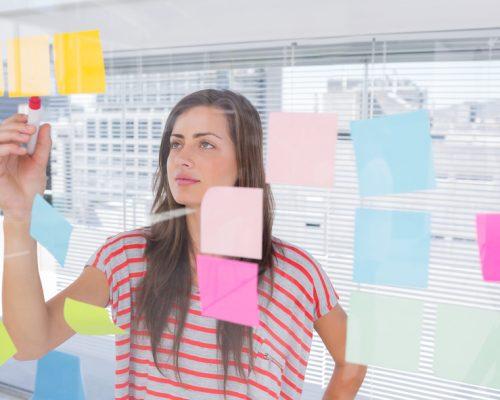 Empreendedor: mulher visualizando papéis de recados e fazendo anotações