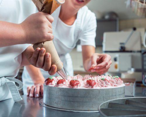 Final do ano: na imagem, pessoas confeitando uma sobremesa de morango