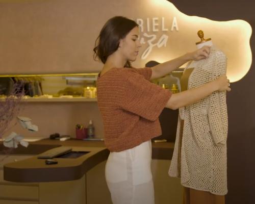 Consumo sustentável: Gabriela Fiúza segura uma camisa de cor clara. Gabriela é branca, está de lado, tem cabelo castanho e usa camisa marrom e calça branca.