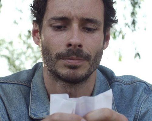 """Cinema: print do curta """"Hiato"""". Um homem de cabelo, barba e bigodes curtos e pretos segura e olha para um bilhete."""