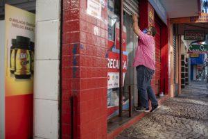 Alvarás: na imagem, homem abrindo portões de um estabelecimento comercial
