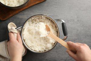 Bolinho de arroz: a imagem mostra uma panela cheia de arroz branco em cima de um balcão cinza e um par de mãos brancas. A mão direita segura um dos lados da panela e a esquerda segura uma colher de pau cheia de arroz.