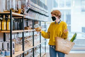 socioambiental: mulher de mascára escolhendo produtos em uma prateleira