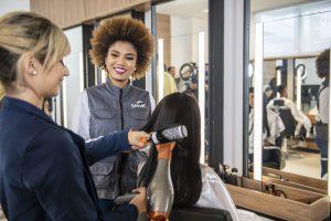 qualificação profissional: na imagem, mulher escova cabelo de outra em salão de beleza enquanto é acompanhada por instrutora do Senac