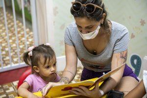 Mês das crianças: na imagem, mulher adulta lê livro infantil para criança