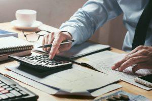 ICMS e refinanciamento: a imagem foco em uma mesa cheia de papéis com uma calculadora e um óculos de grau. A mão de uma pessoa branca tecla na calculadora, enquanto segura uma caneta.