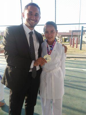 Dandara, com seu treinador Tomaz Maximiano, exibindo a medalha de ouro conquistada. (Foto: Reprodução/Facebook)